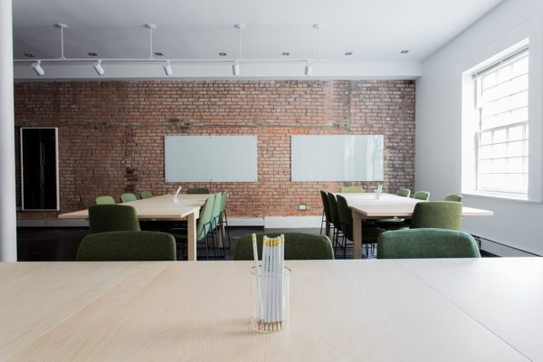 A conference room with tables, chairs, and whiteboards